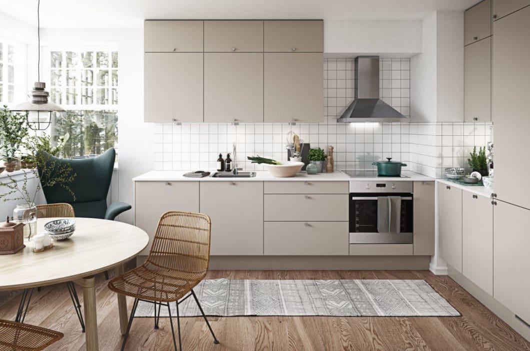 Skandinavische Küchen sind farblich oft reduziert auf unifarbene Töne, beispielsweise Holz, Beige oder Weiß. Ihr klarer und stringenter Aufbau, gemischt mit stilvollen Accessoires wie Teppich und Kacheln, erzeugt eine wohnliche Atmosphäre. (Foto: HTH)