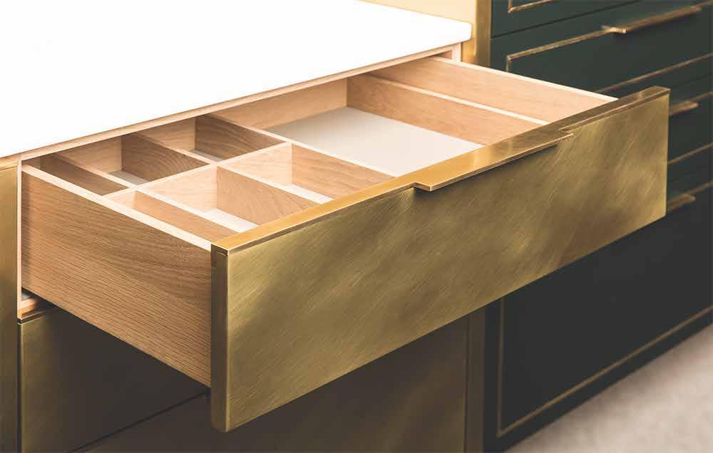 Der Kontrast zwischen der weißen Marmor-Arbeitsplatte, den Schubladen aus Holz und den Verkleidungen aus Messing fasziniert im Materialmix. (Foto: Amuneal)
