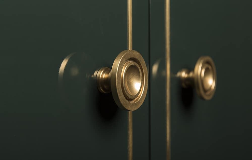 In die dunkelgrün lackierte Tür des Vorratsschranks wurden feine Messing-Linien sowie kreisrunde Messingknöpfe eingearbeitet, die der Küche einen altehrwürdigen Touch verleihen. (Foto: Amuneal)