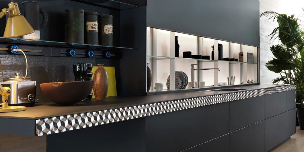 Einen elektrisierenden Kontrast zu dunklem Laminat und Rauchglas setzt diese in aufwändigem Muster gestaltete Schieferblende der verborgenen Küchenschublade bei der Valcucine Genius Loci. (Foto: Valcucine)