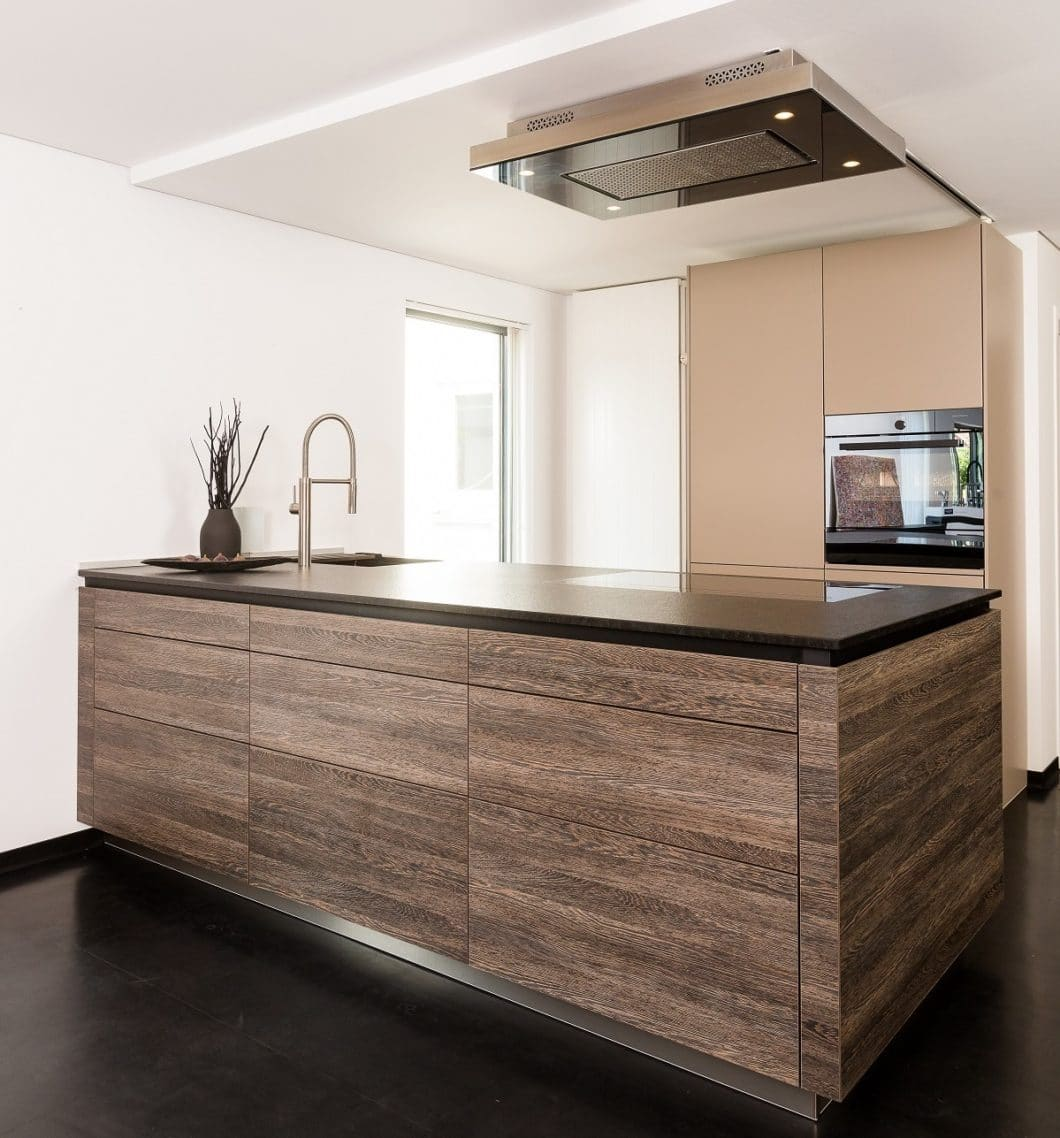 Kleine Küchen müssen entgegen aller Annahmen nicht nur in zurückhaltenden Tönen konzipiert werden. Setzen Sie auf kühle Metallic-Effekte und warmes Holz! (Foto: Lang Küchen & Accessoires)