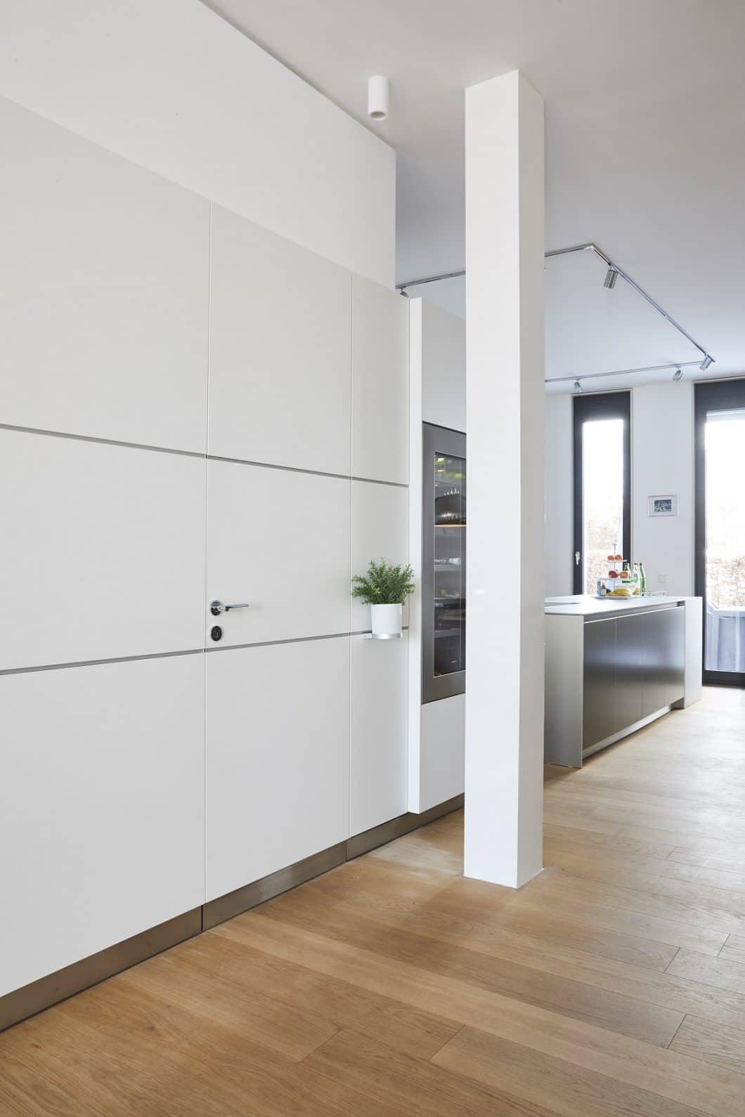 """Besucher treten in das Projekt bulthaup b3 """"Sophienterrasse"""" ein und folgen als erstes der Paneelwand in den Küchenbereich. Hinter der kaum wahrnehmbaren Klinke befindet sich ein extra Gäste-WC, das kaschiert werden sollte. (Foto: Küchen-Atelier Hamburg/ Volker Renner)"""