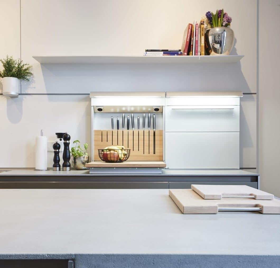 Funktionale Wandpaneele eignen sich nicht nur zur Rückwandgestaltung, sondern können auch mit Küchenutensilien behängt werden. Eine geschlossene Multifunktionsbox offeriert übersichtlichen Stauraum. (Foto: KAH Küchen-Atelier Hamburg)