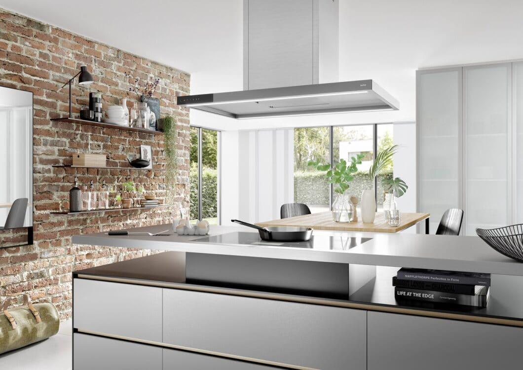 """Inselessen werden immer weniger: wer an einer Kücheninsel kocht, hat die Vorzüge des """"freien Blickfelds"""" für sich entdeckt. Dennoch lassen sich diese Dunstabzugshauben in die Raumgestaltung integrieren. (Foto: berbel)"""