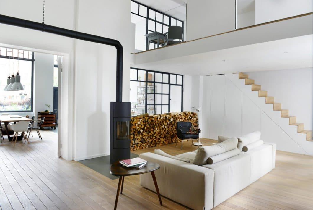 Auch im Wohnzimmer wird der Industrial Style mit einem Stahlofen sowie Stahl-Fensterrahmen weitergeführt. Von hier aus kann man wunderbar den Blick auf die hübsche Wohnküche genießen, ohne den Blicken der Spaziergänger ausgesetzt zu sein. (Foto: Burgheim)