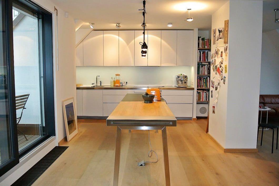 """Die """"wet kitchen"""" hat eine repräsentative Komponente, kann aber auch aus Platzspargründen in zwei Teile geteilt werden: hier ein schönes Beispiel aus Küchenbar- und Mittelpunkt des Raums, im Hintergrund (verborgen durch die seitlich eingezogene Wand) der Arbeitsbereich der Küche. (Foto: bulthaup im Neunten)"""