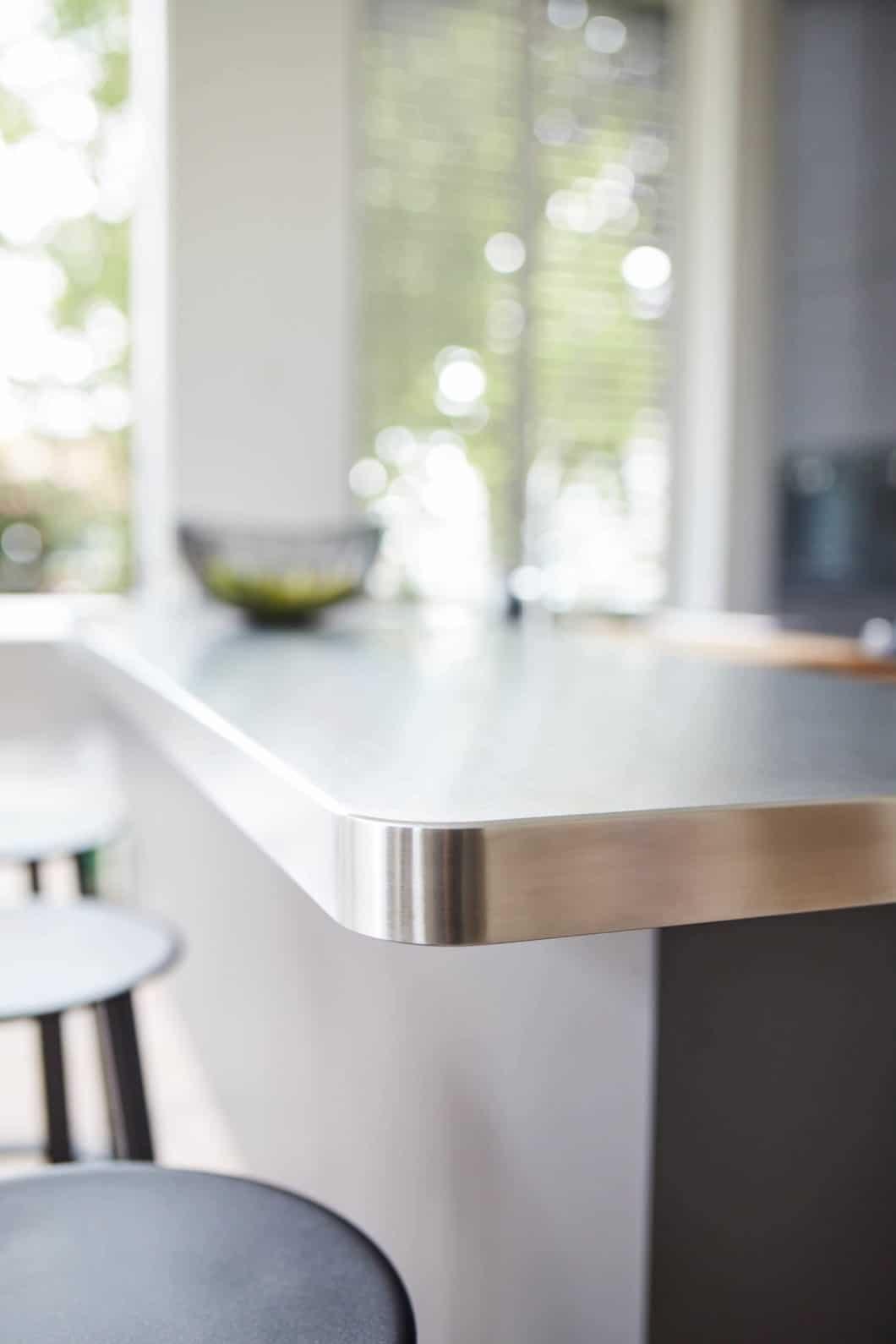 Laminat und Beton dominieren die großflächige Kücheninsel zum Arbeiten und Spülen. Eine warmgewalzte und abgerundete Edelstahl-Barplatte bringt urbanen Chic ein und lädt zum Aperitif. (Foto: Volker Renner/ KAH Hamburg)