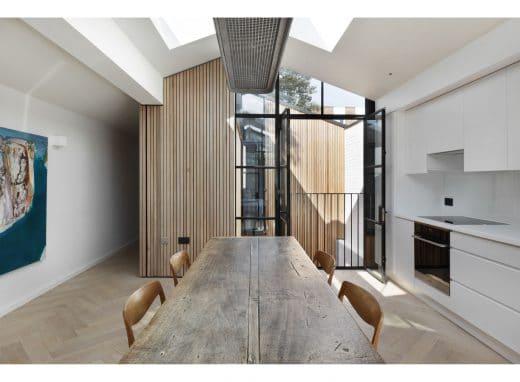 Mattweiße Fronten, Stahl- und Holzelemente: Der industrielle und urban-moderne Look gehen hier fließend ineinander über. (Foto: Alex James für De Rosee Sa)