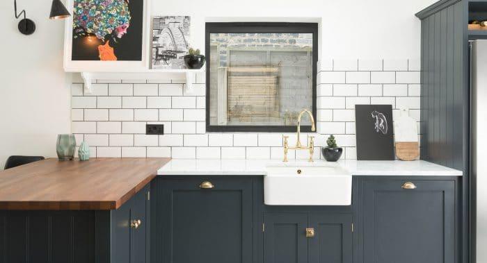 In Graublau geht's auch: Goldene Akzente werden hier nur bei den Griffen und Armaturen gesetzt, ansonsten bleibt die Küche bodenständig mit mattweißen Metro-Kacheln. (Foto: Devolkitchens, East Dulwich Kitchen)