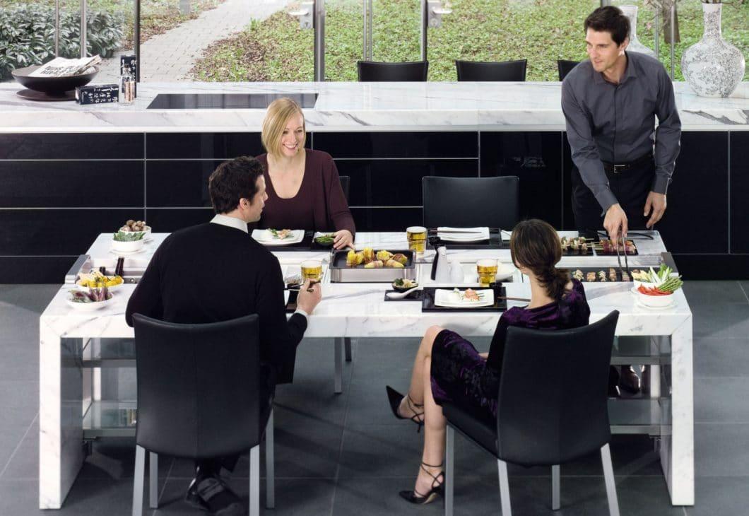 Mit dem Dining Desk sind Essen und Getränke immer in Reichweite - das entspannt auch die Gastgeber. (Foto: Poggenpohl)