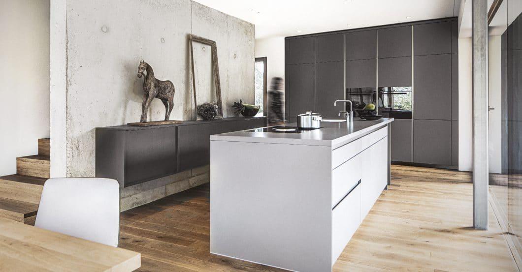 Wenn eine Kücheninsel von beiden Seiten zugänglich sein soll, können die Schubladen jeweils nur verkürzt in der Tiefe verbaut werden. Dazwischen muss die Technik des Kochfeldabzugs Platz finden. (Foto: Dross&Schaffer München Ost)