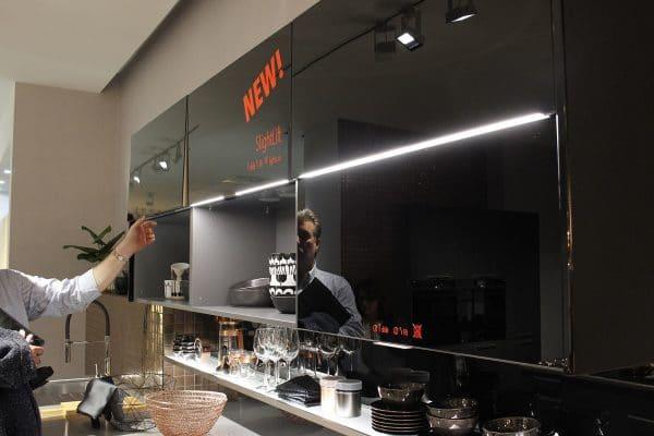 """Der Häcker Slightlift ist eine Kombination aus Oberschrank und Regal. Beide Fächer können zunächst zugezogen sein (rechts im Bild). Verschiebt man die untere Regaltür nach oben, geht die LED-Lichtleiste im Oberschrank an und beleuchtet die """"Küchenvitrine"""". (Foto: Scheffer)"""