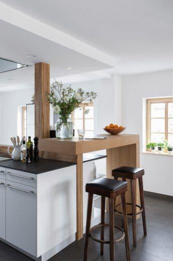 Eine praktische Küchenbar in Form eines Tresens lädt zum kurzzeitigen Verweilen ein und führt den Landhaus-Stil im ansonsten minimalistischen Loft weiter. (Foto: Hillig)