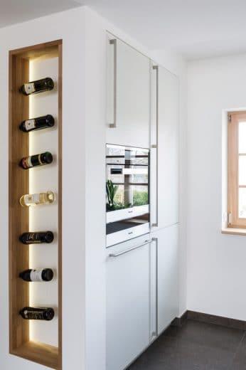 Das am Küchenschrank seitlich integrierte Weinregal ist nicht nur funktional verstaut, sondern auch optisch ein Galnzpunkt der Küchenplanung. (Foto: Hillig)