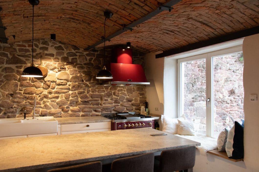 Freigelegte Steinwände, alte Ziegeldecke, moderne und hochwertige Möbel: die Kontraste sind enorm, und dennoch blieb genug Platz für eine gemütliche Sitzecke. (Foto: Küchenhaus Süd)