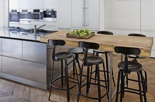 Edelstahl, schwarze Metallstühle und eine knorrige Holzplatte werden von Isabelle Stanislas in ihrer Pariser Altbauwohnung zu hohen Decken und viel Licht verknüpft. (Foto: awmagazin)