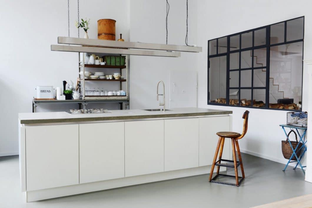 Der Küchenboden aus Estrich grenzt den freistehenden Küchenblock vom direkt gegenüberliegenden Esstisch ab. Der grau gewölkte Beton als Arbeitsplatte greift das industrielle Thema des Küchenbereichs auf. Die Fenster zum Wohnzimmer hin hat der Architekt aus Lichtgründen nachträglich einsetzen lassen. (Foto: Burgheim)