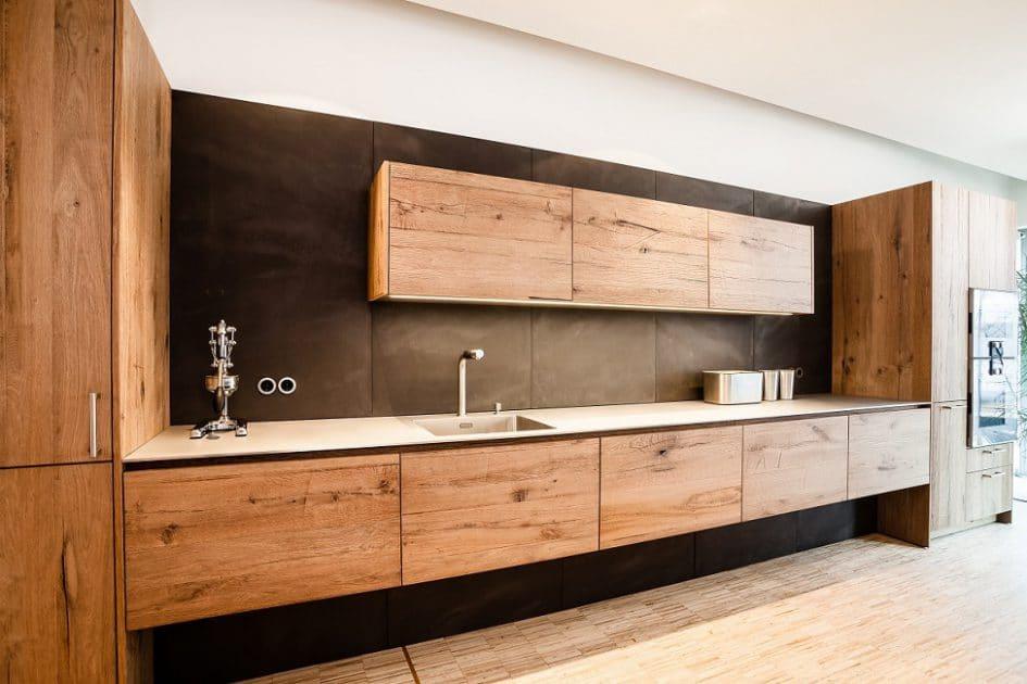 Eine warme Küchenwand aus Altholz mit einer Kücheninsel und Küchenwänden aus gespachteltem Beton. (Foto: Lang Küchen)