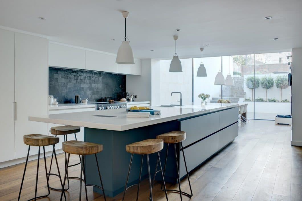 Mit wenigen Handgriffen lässt sich eine Küche bei einer Renovierung erneuern: die dunkle Küchenrückwand auf diesem Bild verleiht dem Küchenraum beispielsweise nochmal einen industriellen Touch. Die Arbeitsplatte wiederum kann auch einfach ausgetauscht werden. (Foto: Roundhouse Design)