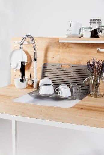 Die abgeschrägte Spüle hilft Küchennutzern, das Geschirr mit wenig Kraft oder nur einer Hand hinauszuziehen oder an der Schräge selbst zum Abtropfen aufzustellen. Der abnehmbare Schlauch befüllt Töpfe mit Wasser, die schon auf dem Herd bereitstehen. (Foto: Dirk Biotto)