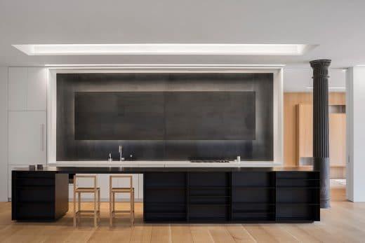 Die eindrucksvolle Stahlplatte an der Küchenwand wird mit LEDs hinterleuchtet und verleiht der Küche eine geheimnisvolle Aura. (Foto: Paul Warchol for Desai Chia Architecture)