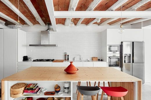 Eine weiße, moderne, grifflose Küchenwand im skandinavischen Stil trifft auf mediterrane Kiefernholzplatten und unverputzten, industriellen Backstein. (Foto: José Hevia)