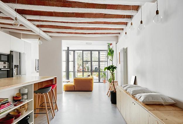 Die Küche ist in dem länglichen Raum seitlich angeordnet und öffnet sich zum gemütlich-stilvollen Wohnraum und einem hellen Garten-Atelierfenster hin. (Foto: José Hevia)