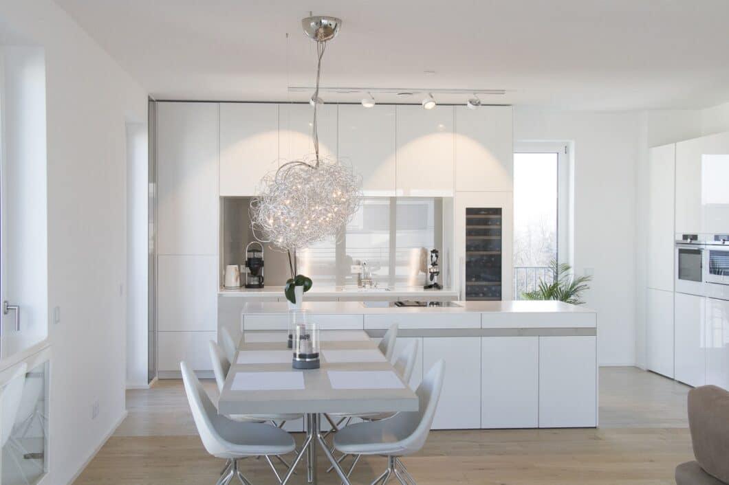 Weiße Küchen harmonieren in ihrem Glanz mit schroffem Beton, der dem Küchenraum eine architektonische Note verleiht. Designleuchten runden das Arrangement luxuriös ab. (Foto: Küchenhaus Süd)