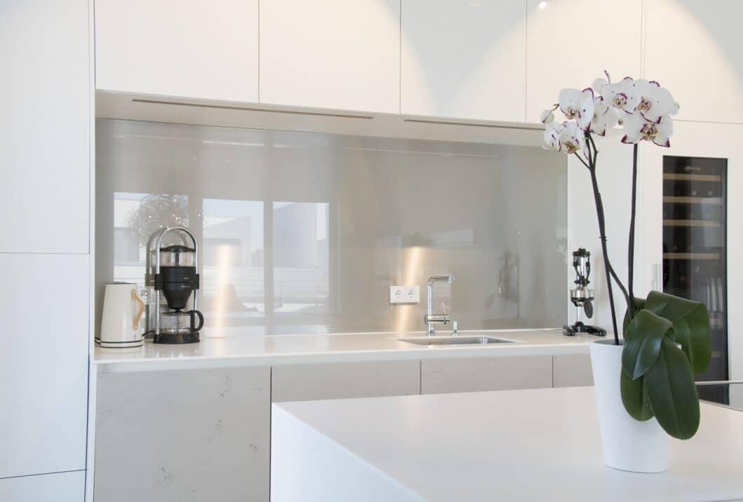 Sowohl die weißen Hochglanzfronten als auch die Küchenrückwand in spiegelndem Grau reflektieren das Licht der hellen Loftküche und lassen den Raum ästhetisch & glanzvoll wirken. (Foto: Küchenhaus Süd)
